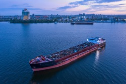 A ship loaded with scrap metal is anchored in the water area of the Dnieper River against the background of the evening city of Dnipropetrovsk