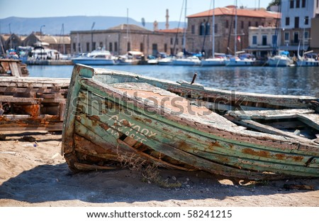 A shipwrecked rowing boat lies beached at the Greek port of Chania on the isle of Crete.