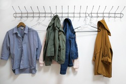 A shirt, jackets and a hanger hang on a metal wall hanger. Women's clothes hanging on a wall hanger. Hooks with clothes hangers on a white wall.
