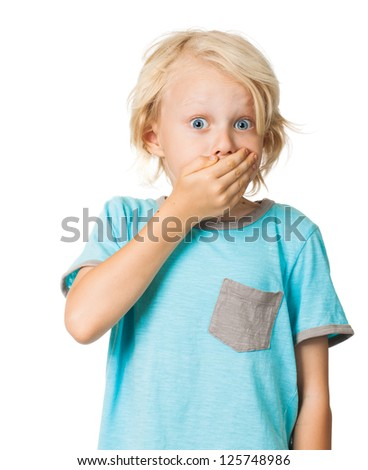 A shocked frightened young boy covering his mouth with his hand and staring wide eyed at the camera. Isolated on white.