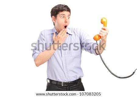 A shocked man holding a telephone tube isolated on white background