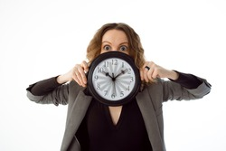 A shocked woman with bulging eyes holds in her hands a large clock with fast moving arrows on a white background. Isolated on a white background. The concept of deadline, failure, procrastination