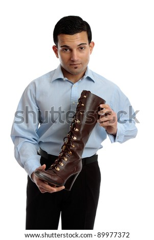 A shoe salesman holding a brown leather lace up boot.  White background.