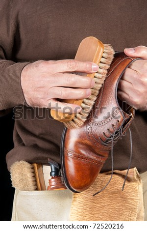 A shoe shiner works on the final buffing of a leather dress shoe - stock photo