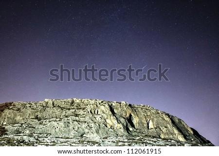 A shooting star streaks across the sky over the GHar Lapsi cliff face in Malta