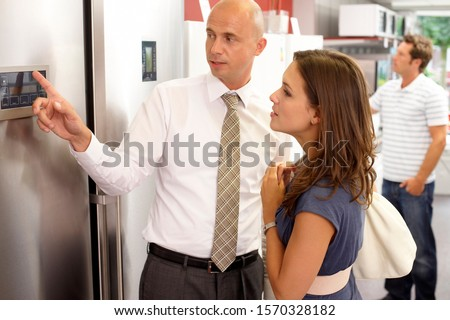 A shop assistant showing a female customer a new fridge