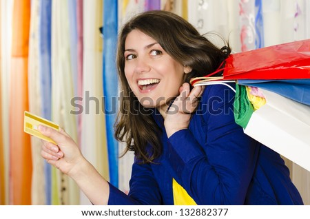 A shopaholic girl holding a credit card coming from shopping