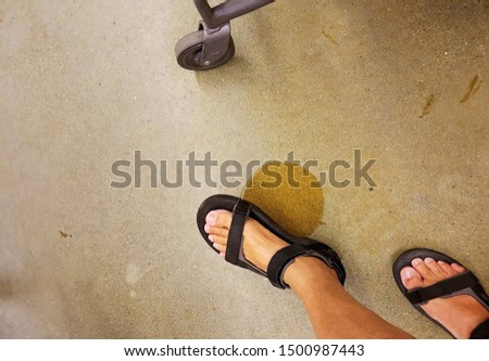 A shoppers foot about to step on a slippery wet spot on the floor inside a grocery.