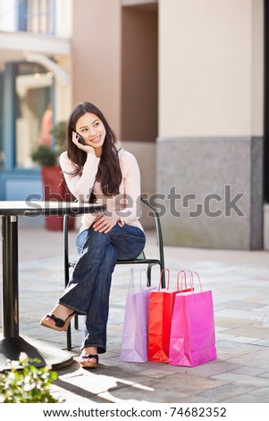 A shopping asian woman talking on her phone