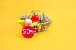 a shopping basket with fruit and gift boxes on a yellow background and a red sign that says 50 percent off