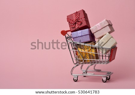 a shopping cart full of gifts of different colors on a pink background, with a negative space #530641783