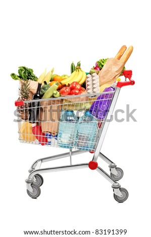 A shopping cart full with groceries isolated on white background - stock photo