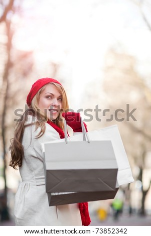 A shopping caucasian woman carrying shopping bags at an outdoor shopping mall - stock photo