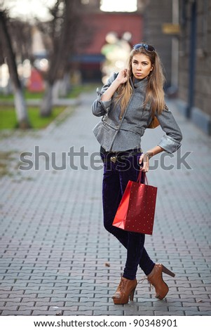 A shopping woman carrying shopping bags outdoor