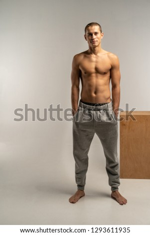 A shortcut hair man with a naked body in gray pants posing on white background