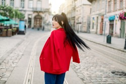 A shot in the motion of charming attractive young asian woman, wearing red blazer and jeans, walking in the old European city. Outdoor city portrait of fashion woman model