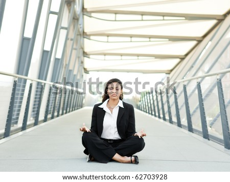 A shot of a beautiful black businesswoman meditating