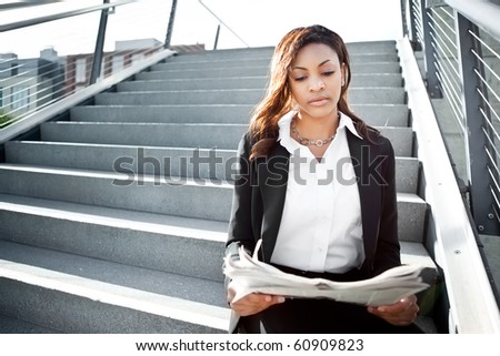 A shot of a beautiful black businesswoman reading newspaper outdoor