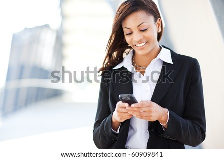A shot of a beautiful black businesswoman texting stock photo