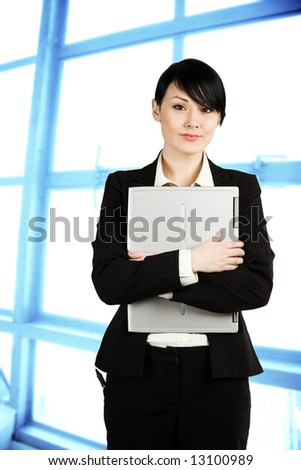 A shot of a beautiful businesswoman carrying a laptop in the office - stock photo