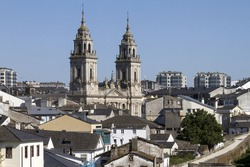 A shot of a beautiful Cathedral of Lugo, Galicia surrounded by buildings under the clear sky