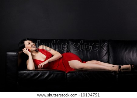 A shot of a beautiful girl lying on the sofa and talking on the cellphone
