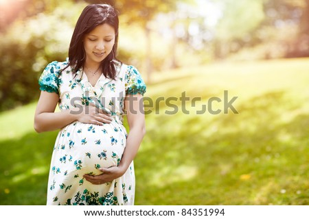 A shot of a beautiful pregnant Asian woman outdoor