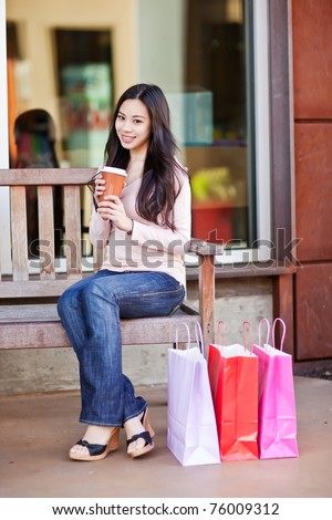 A shot of a beautiful shopping asian woman drinking coffee outdoor