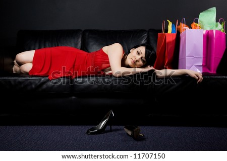 A shot of a beautiful woman resting on a couch after shopping