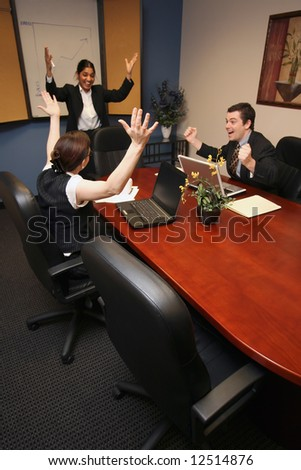 A shot of a businesswoman presenting to a businessman and businesswoman.  All three have their hands up in excitement.