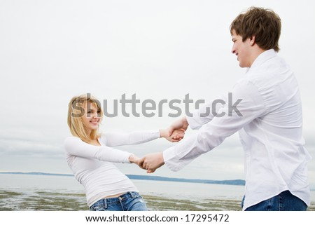 A shot of a caucasian couple in love having fun on the beach