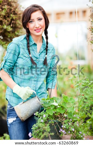 A shot of a caucasian woman gardening in the green house