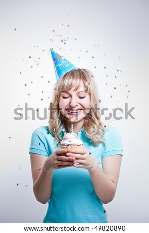 A shot of a girl celebrating her birthday holding a cupcake