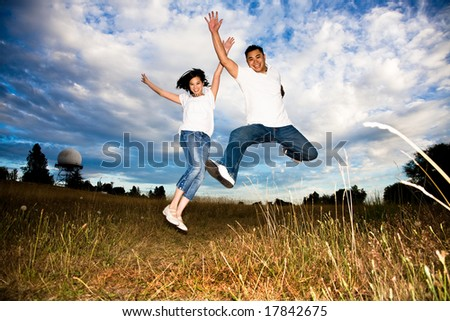 A shot of a happy asian couple jumping for joy