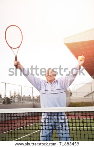 A shot of a happy asian senior tennis player playing tennis
