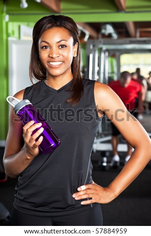 A shot of a happy black female athlete holding a water bottle in a gym - stock photo