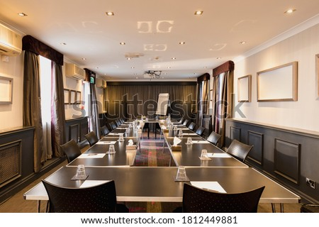 A shot of a large room with a table set up and ready for a business meeting with papers and glasses on each desk. Foto d'archivio ©