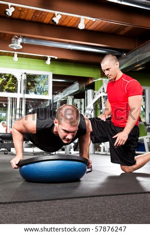 A shot of a male personal trainer assisting a male athlete doing push-up - stock photo
