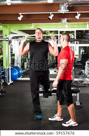 A shot of a male personal trainer assisting a male athlete training