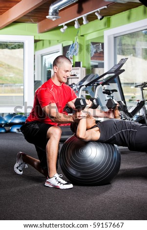 A shot of a male personal trainer assisting a woman lifting weights