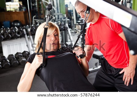 A shot of a male personal trainer assisting a woman pulling weights