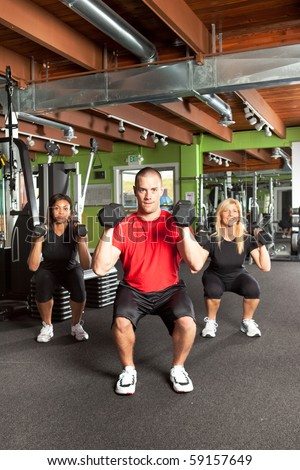 A shot of a male personal trainer training with two female athletes in the gym