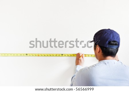 A shot of a man using measurement tape for home improvement