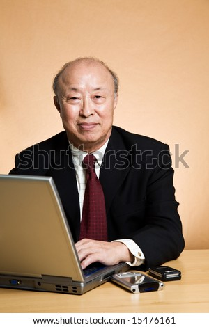 A shot of a mature asian businessman working on his laptop
