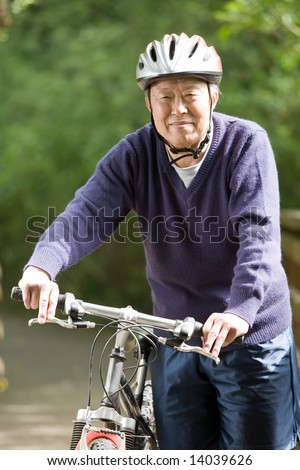 A shot of a mature asian man riding a bike