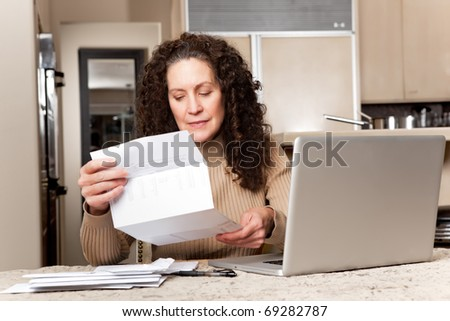 A shot of a middle age caucasian woman paying bills at home - stock photo