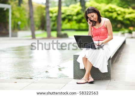 A shot of a mixed race woman talking on the phone and working on her laptop