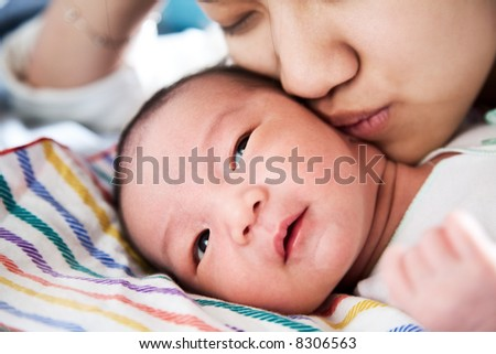 A shot of a mother affectionately kissing her baby boy
