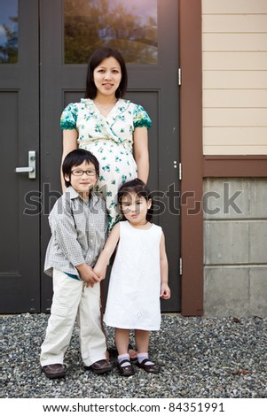 A shot of a pregnant Asian mother with her two kids outdoor