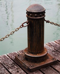 a shot of a rusty pole with chains on the blurred background of water